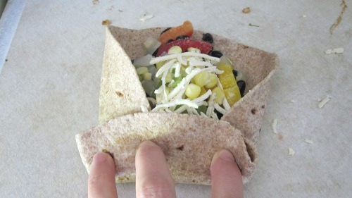 The second step in folding bean burritos is to fold the bottom up over the side folds to hold in the filling.