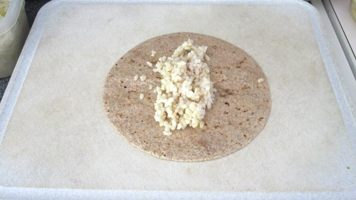 Step one of making bean burritos is to place in a few tablespoons of brown rice.