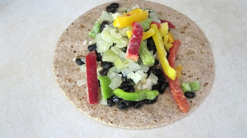 Step three of making bean burritos is to add in your chosen vegetables.